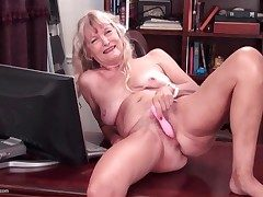 Naked granny on a desk masturbates her cunt